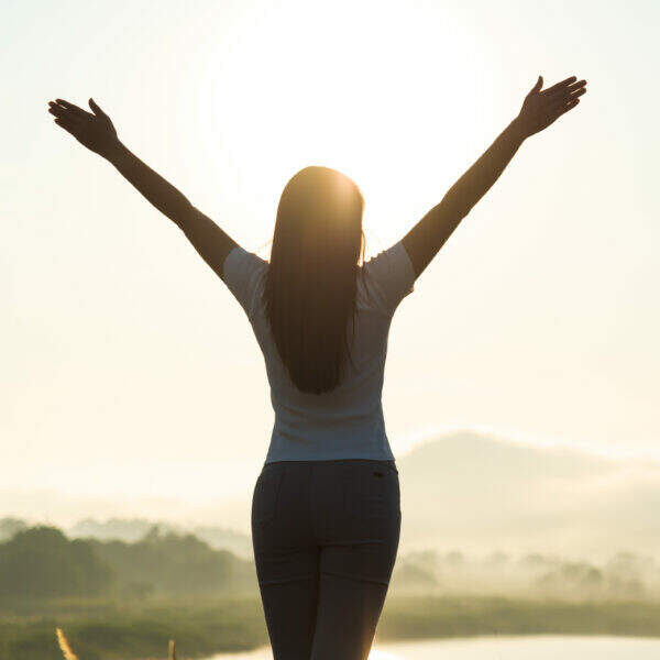 Silhouette of happy woman spreading arms and watching the mountain. Travel Lifestyle success concept adventure active vacations outdoor freedom emotions.